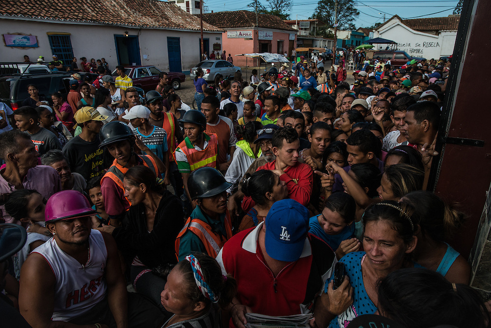 "LA VELA, VENEZUELA - SEPTEMBER 27, 2016: Hundreds of Venezuelans lined up in front of a grocery store in La Vela to wait to see if government price-controlled food would be delivered. Despite having the largest known oil reserves in the world, Venezuela is suffering from hyperinflation and a severe economic crisis making affordable food difficult for most middle and working class families to access.  Well over 150,000 Venezuelans have fled the country in the last year alone, the highest in more than a decade, according to scholars studying the exodus. As Hugo Chávez's Socialist-inspired revolution collapses into economic ruin, as food and medicine slip further out of reach, the new migrants include the same impoverished people that Venezuela's policies were supposed to help. ""We have seen a great acceleration,"" said Tomás Paez, a professor who studies immigration at the Central University of Venezuela. He says that as many as 200,000 Venezuelans have left in the last year, driven by how much harder it is to get food, work and medicine — not to mention the crime such scarcities have fueled.  PHOTO: Meridith Kohut"