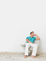 Full length of thoughtful young man sitting on chair