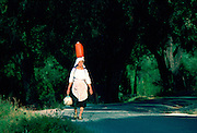 A local woman walking while carrying a can on her head and a pot in her hand, Corfu Island, Greek Islands
