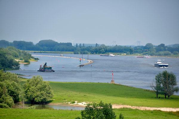Nederland, Varik, 6-6-2018 Vrachtschepen varen over de Waal richting Duitsland . In dit deel van de Waal zijn de kribben verwijderd en vervangen door een paralel met de oever lopende watergeleiding .Foto: Flip Franssen