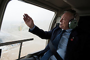 Dallas Cowboys owner Jerry Jones wipes fog off the window during a helicopter ride over his new team headquarters and practice facility in Frisco, Texas on December 1, 2015.  (Cooper Neill for The New York Times)