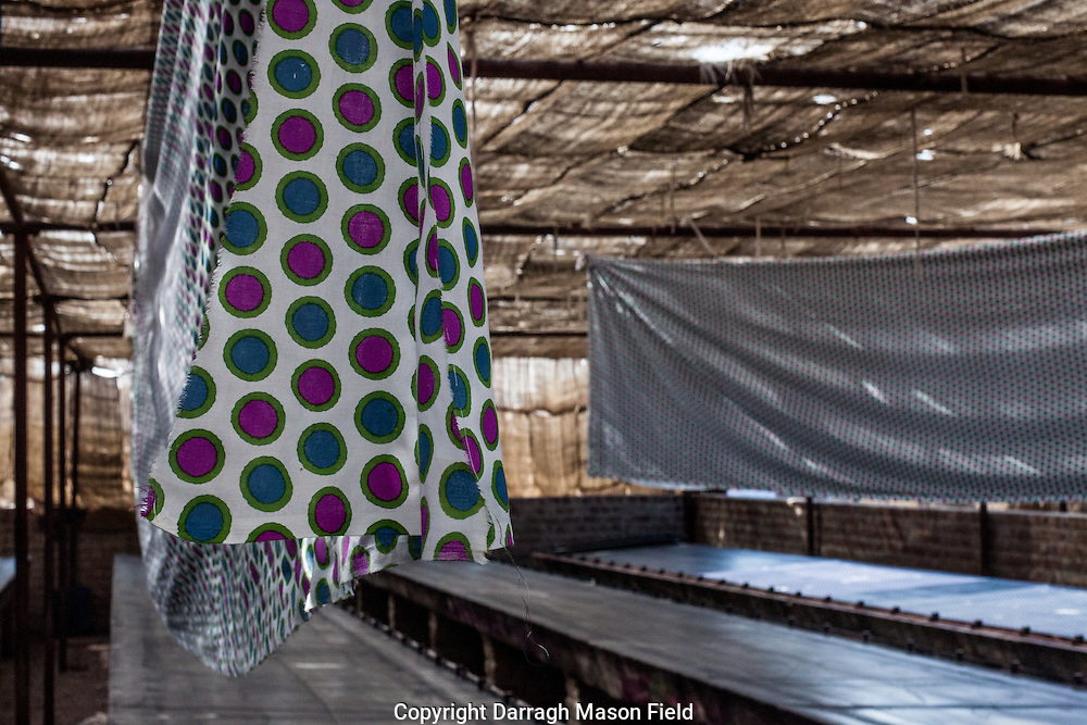 A spot patterned sari hang dries after screen printing.