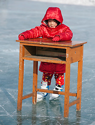 Young girl learning to ice skate by holding a wooden table in Harbin northern China