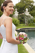Mid adult bride at poolside holding bouquet looking over shoulder