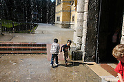 Austria, Salzburg, Morzg, Hellbrunn Castle, young tourists playing in the Trick fountain spray