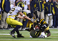 October 10, 2009: Iowa wide receiver Marvin McNutt (7) is pulled down by Michigan cornerback Donovan Warren (6) as Michigan safety Jordan Kovacs (32) comes to assist during the first half of the Iowa Hawkeyes' 30-28 win over the Michigan Wolverine's at Kinnick Stadium in Iowa City, Iowa on October 10, 2009.