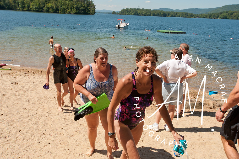 Rosemarie DeMars, Nancy Jones Hansen, and Rick and Wendy Vandepull are greated by a large crowd following their seven mile swim of Squam Lake on Thursday, August 19, 2010.  (Alan MacRae/for the Citizen)