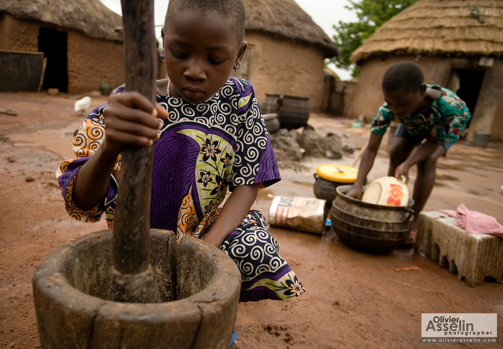Abibata Alhassan (left) prepares food while her sister Aisha washes pots at their family's home after coming back from school in the village of Nyologu, northern Ghana, on Wednesday June 6, 2007.