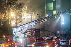 © Licensed to London News Pictures . 01/01/2018. Liverpool, UK. Fire hose jets are sprayed in to the car park (pictured with charred metal facia boards in the centre of the picture . Scene at the Liverpool Echo Arena car park where firefighters are working to extinguish a fire that started late on New Year's Eve and that destroyed all 1,400 cars parked in the multi-story car park. The Liverpool International Horse Show taking place at the Arena was abandoned and people and horses evacuated as dozens of fire crew worked to control the blaze . Photo credit: Joel Goodman/LNP