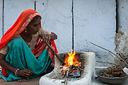 Rajasthani village woman preparing cooking fire in the morning. Pushkar, Rajasthan. INDIA