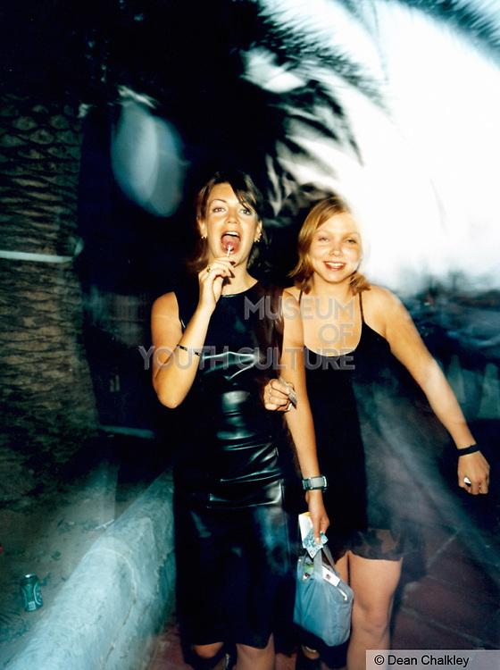 Two girls walking down the street one sucking a lolli pop Ibiza 1999