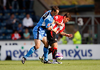 Photo: Richard Lane/Richard Lane Photography. Wycombe Wanderers v Brentford. Coca Cola Fotball League Two. Brentford's Charlie MacDonald is challenged by Wycombe's  David McCracken.