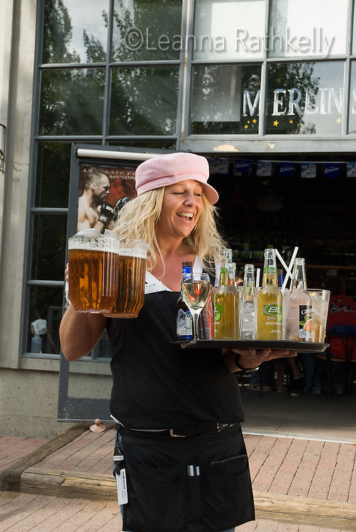 A waitress carries an armful of drinks at the outdoor patio of Merlins Restaurant, at the base of Blackcomb Mountain in Whistler, BC Canada