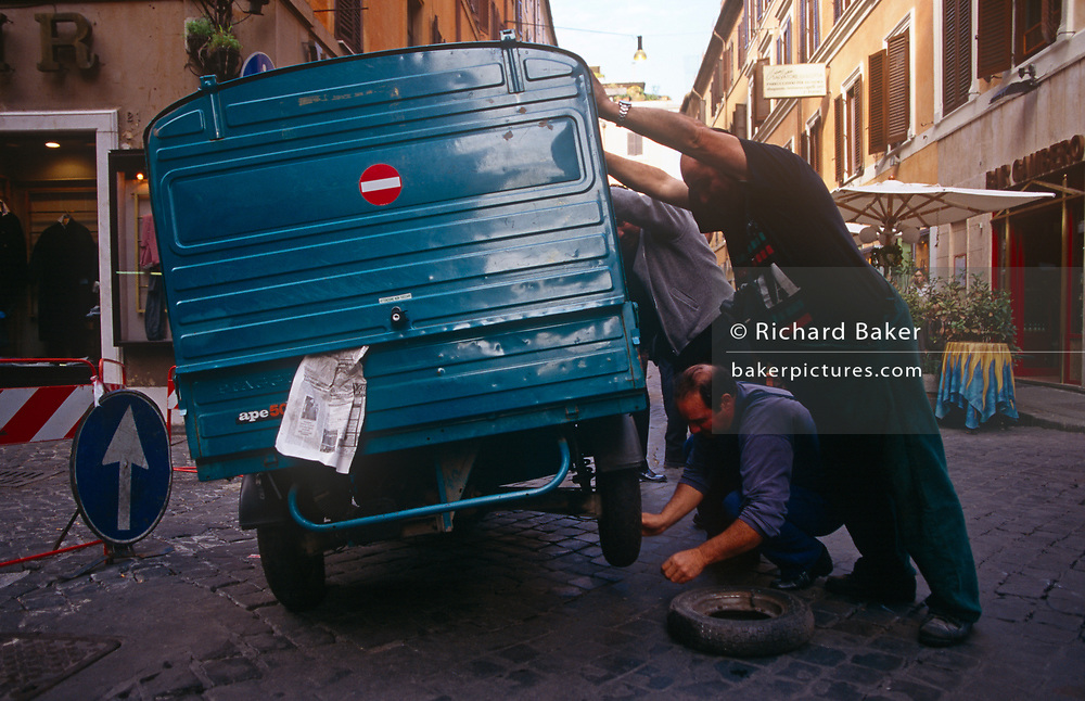 A team of men push over a small Ape van to change a flat tyre in a side street of the Italian capital, on 3rd November 1999, in Rome, Italy.