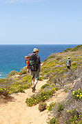 Two people walking the cliff top coastal footpath trail, The Fisherman's Walker or Ruta Vicentina,  near Odeceixe, Algarve, Portugal, Southern Europe