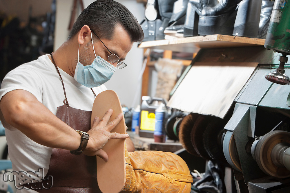 Skilled cobbler wearing mask working on shoe sole in workshop