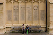 Locals from Cirencester sit below the first world war memorial on the church wall in the city centre.