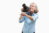 Senior female photographer with camera gesturing against white background