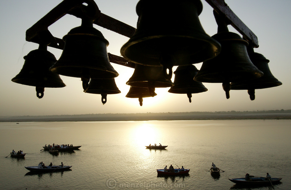 These bells adorn the top of a shrine overlooking the Ganges river at the Harishchandra Ghat, Varanasi, India. The Harishchandra Ghat (also known as the Harish Chandra Ghat) is the smaller and more ancient of the two primary cremation grounds in Varanasi, on the banks of the Ganges River.