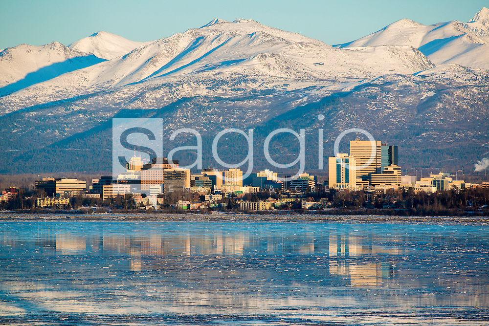 The Anchorage Skyline and Chugach Mountains are reflected in Cook Inlet.