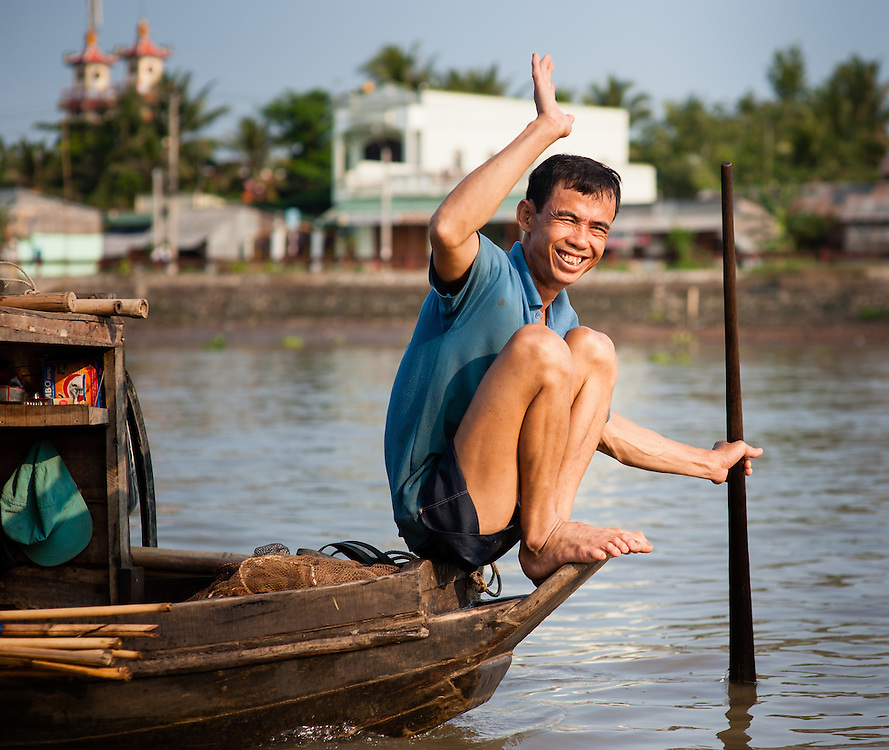 Man waving from boat on Mekong Delta (Vietnam)