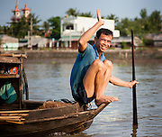 Man waving from boat on Mekong Delta (Vietnam)