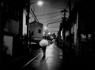 "Homeless on streets / Streets like a nursing home: Destitute senior walks the street in San'ya on a rainy winter night empty but for the occasional old man returning to a cheap ""do-ya"" boarding house.  Tokyo, Japan.  Do-ya have become de facto dumping grounds for unwanted old men.  In the northeast of Tokyo is a community that used to be called San'ya, where the unwanted lower Japanese castes of butchers and leather tanners had to live.  Now it is known for low cost  boarding houses.  Though San'ya is thought of as a refuge for alcoholics, peel back a thin veneer and it immediately becomes evident what San'ya really is, a repository for unwanted, unloved old men.  Many do-ya are little more than unregistered nursing homes, minus the medical staff.  It keeps those, who can afford the Y1,000 - Y2,000/night off the streets at night."