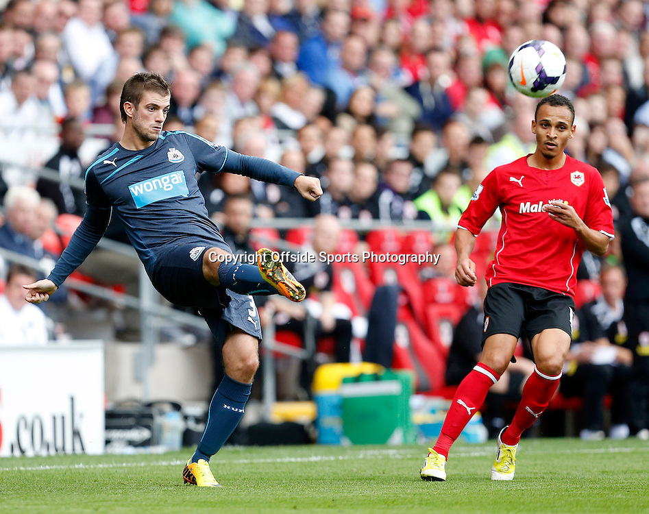 5th October 2013- Barclays Premier League - Cardiff City Vs Newcastle United - Davide Santon of Newcastle United crosses as Peter Odemwingie of Cardiff City looks on - Photo: Paul Roberts / Offside.