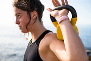 Young woman doing a summer morning outdoor workout with a coastal ocean backdrop