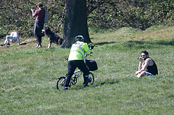 © Licensed to London News Pictures. 05/04/2020. London, UK. A police officer talks to a member of the public sitting on Hampstead Heath, London, during a pandemic outbreak of the Coronavirus COVID-19 disease. The public have been told they can only leave their homes when absolutely essential, in an attempt to fight the spread of coronavirus COVID-19 disease. Photo credit: Ben Cawthra/LNP