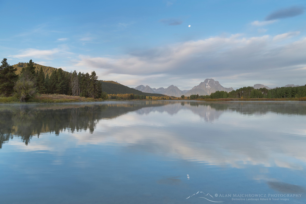Full moon and Mount Moran reflected in still waters of the Snake River at Oxbow Bend at sunrise, Grand Teton National Park Wyoming