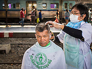 16 APRIL 2015 - BANGKOK, THAILAND:  A man gets a haircut at a barber school that sets up on the platform at Hua Lamphong Train Station in Bangkok. Travelers get free haircuts and the barber students get to practice on real heads.    PHOTO BY JACK KURTZ