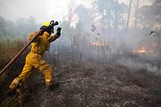 Arp FD firefighter PJ Terry runs towards the flames as they advance towards CR 26 on Wednesday.© 2011 Jaime R. Carrero/Tyler Morning Telegraph