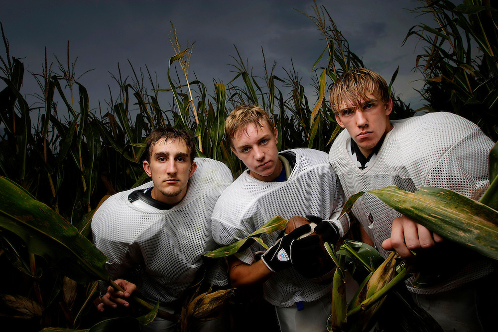 Griswold High School seniors, from left, Brandon Ridlen, Tyler Mosier and Keith Rush emerge from cornstalks near their school and practice field. | Chicago Freelance Photographer | Alyssa Schukar | Photojournalist