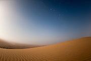 Moonrise in the mist over Sand Dunes, Skeleton Coast National Park, Namibia.