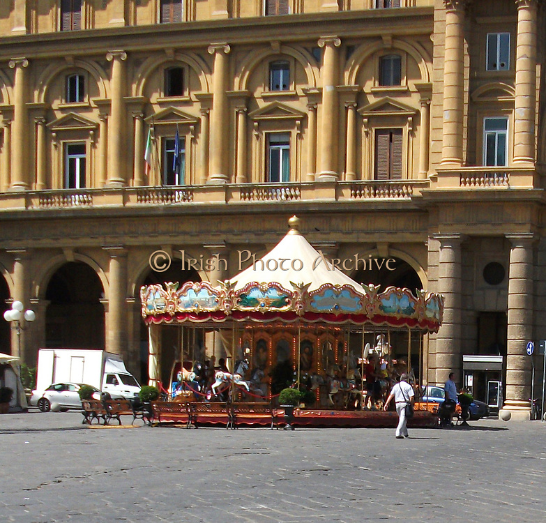 An antique carnival carousel in the middle of a plaza in Florence, Italy.