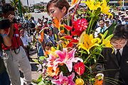 14 SEPTEMBER 2003 - CANCUN, QUINTANA ROO, MEXICO:  A member of Lee Kyung-hae's family carries a bouquet of flowers during a memorial service for Lee Kyung-hae, the South Korean farmer who committed suicided during a protest against liberalized agricultural trade at the WTO ministerial in Cancun. Tens of thousands of protesters, mostly farmers, came to Cancun for the fifth ministerial of the World Trade Organization (WTO). They were protesting against developed nations pushing to get access to agricultural markets in developing nations. The talks ultimately collapsed after no progress with no agreements reached between the participants.          PHOTO BY JACK KURTZ