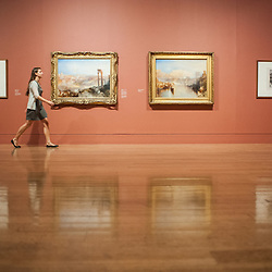 London, UK - 8 September 2014: a gallery assistant walks past 'Modern Rome - Campo Vaccino' (L) and 'Ancient Rome: Agrippina Landing with the Ashes of Germanicus' (R) by J.M.W. Turner, brought together for the first time in a generation.