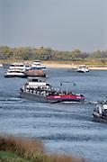Nederland, the netherlands, Nijmegen, 18-10-2018 Binnenvaartschepen varen in de Waal langs de oever en de ooijpolder. Door de aanhoudende droogte staat het water in de rijn, ijssel en waal extreem laag .Laagterecord en de laagste officiele stand ooit bij Lobith gemeten, 6,73 m boven NAP . Schepen moeten minder lading innemen om niet te diep te komen . Hierdoor is het drukker in de smallere vaargeul . Door te weinig regenval in het stroomgebied van de rijn is het record verbroken . Foto: Flip Franssen