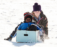 Omario Brooks gets a helpful push from Sophia Lehr during Gilford Parks and Recreation Cardboard Derby race at the Outing Club sledding hill on Wednesday morning.  (Karen Bobotas/for the Laconia Daily Sun)