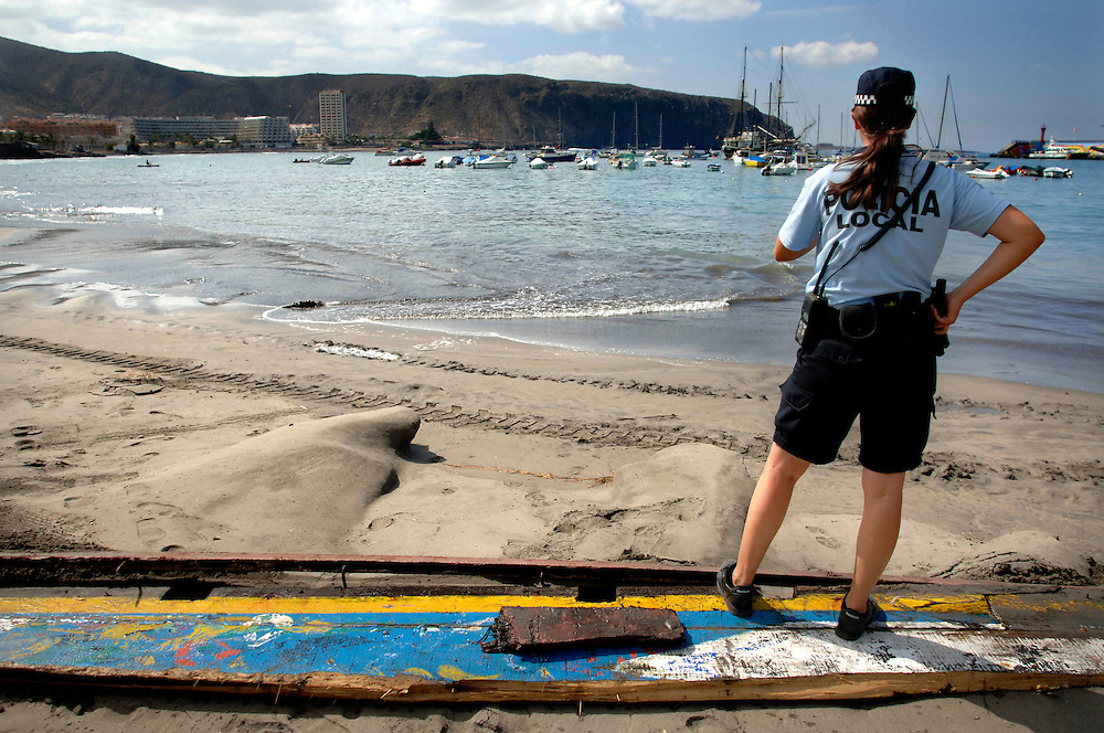 """Tenerife / Los Cristianos June 7, 2006 - Police-Woman in front of the beach - A fishing boat called """"Cayucos"""" by the inhabitants of the island, with 85 would-be immigrants from West Africa intercepted by Spanish police of the coast of Tenerife in the Canary Islands are seen in an open wooden fishing vessel as they approach the port of Los Cristianos. They arrived on June, carrying 85 would-be immigrants, in the archipelago which has received more than 7,000 Africans so far this year, more than half to the tourist resort island of Tenerife. At least 1,000 more are believed to have died trying to make the sea crossing, mostly in small fishing boats"""