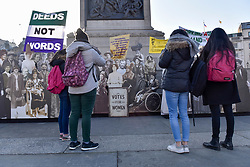 """© Licensed to London News Pictures. 06/02/2018. LONDON, UK.  Members of of the public view a pop-up exhibition featuring 59 life-sized images of campaigners, along with famous rallying slogans such as """"deeds not words"""" in Trafalgar Square marking 100 years since the Representation of the People Act was passed, granting some women over the 30 in the UK the right to vote for the first time.  Photo credit: Stephen Chung/LNP"""