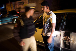 A young man wearing a style of shirt and hat associated with Mexico's  Narco Culture argues with a traffic police during a routine drunk driving check point.