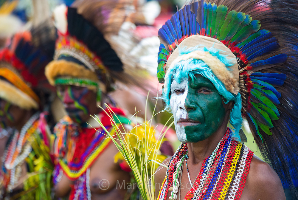 Woman with her face painted green and white. She is standing in a group wearing an elaborate tribal headdress made with feathers from Eclectus Parrot and Cassowary at the Goroka show in Papua New Guinea.