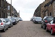 A cobbled back street lined with cars in Skipton, North Yorkshire, UK.