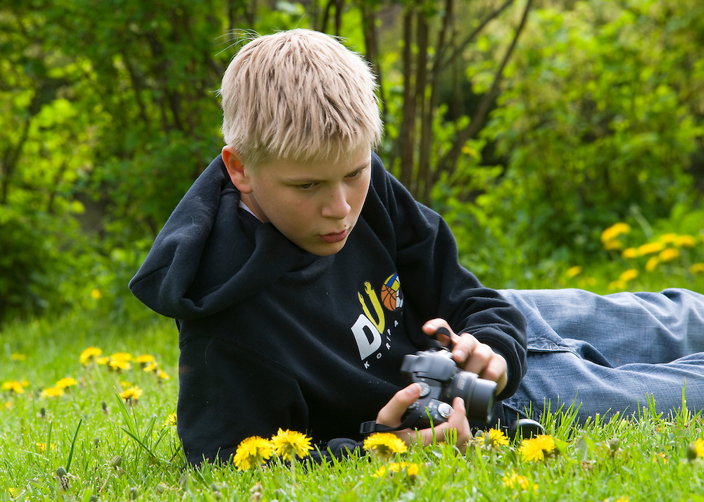 Boy taking pictures amongst dandelions, Estonia