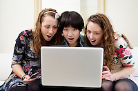 Surprised friends looking at something in laptop
