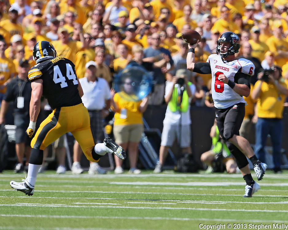 August 31 2013: Northern Illinois Huskies quarterback Jordan Lynch (6) passes the ball over Iowa Hawkeyes linebacker James Morris (44) during the first quarter of the NCAA football game between the Northern Illinois Huskies and the Iowa Hawkeyes at Kinnick Stadium in Iowa City, Iowa on August 31, 2013. Northern Illinois defeated Iowa 30-27.