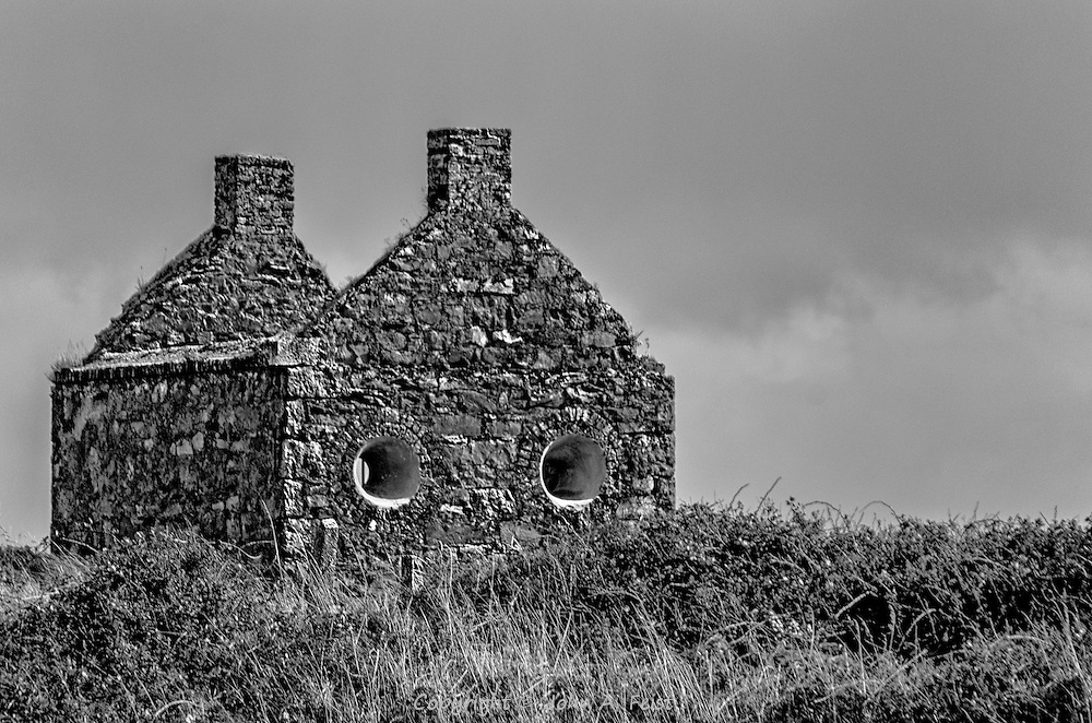 An abandoned house outside of Sligo, County Sligo, Ireland.  The configuration of the house and windows gives the impression that it has a face.  Presenting this image in black and white gives it a very different feel.