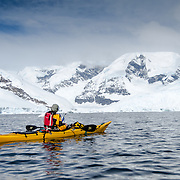 A kayaker heads towards the scenic mountains at Neko Harbour, Antarctica.